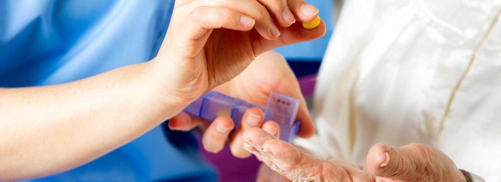 Nurse giving an elderly medication