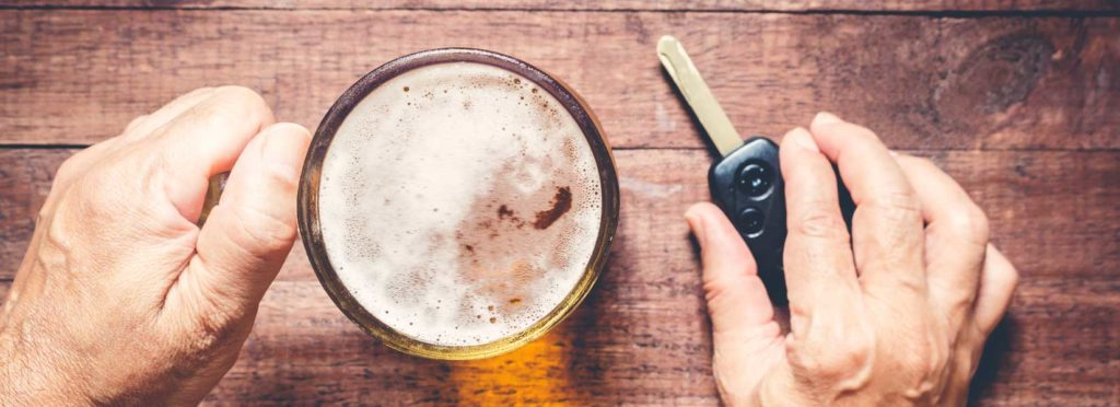 Person with glass of beer holding car key