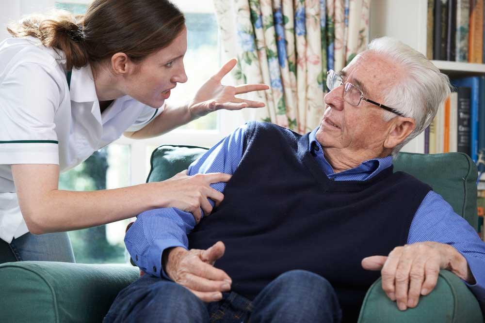 A nurse being abusive to an elderly man.