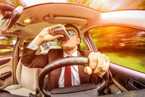 A man drinking while driving.